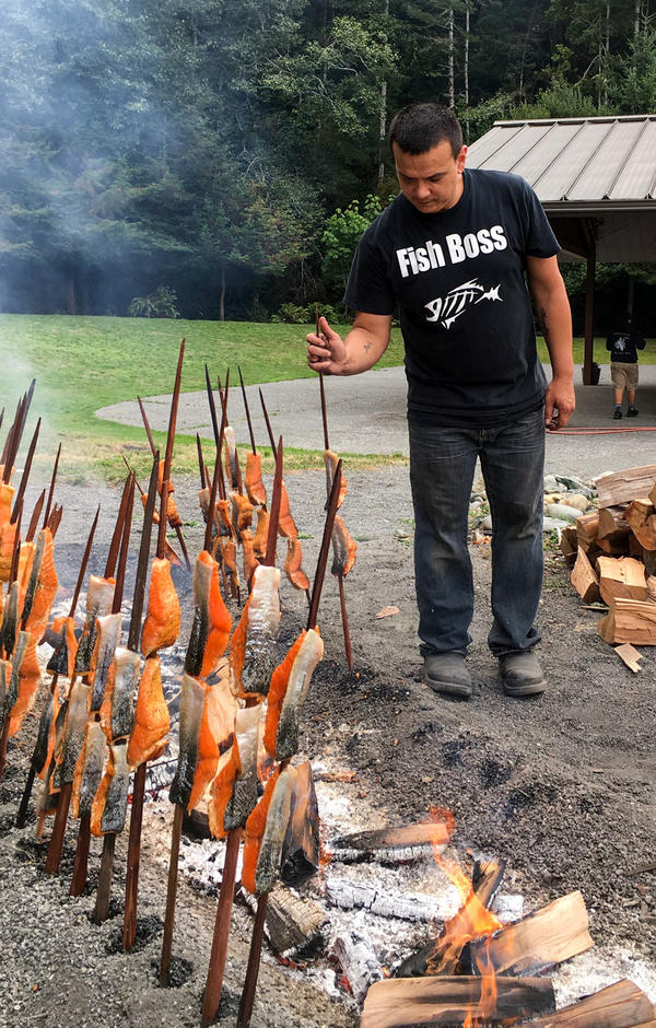 At the 55th Annual Yurok Salmon Festival, Oscar Gensaw cooks salmon the traditional way, on redwood skewers around a fire pit. This year, though, the tribe had to buy salmon from Alaska.