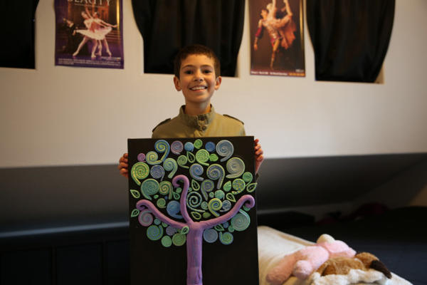 <p>Asjia Chapin, age 10, in her room, displaying one of her latest collages. She also writes poetry and does other art work.</p>