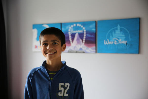 "<p>Kaliq Chapin, age 12, in his room in front of Disney posters. ""Monsters, Inc."" is one of his favorites movies.</p>"