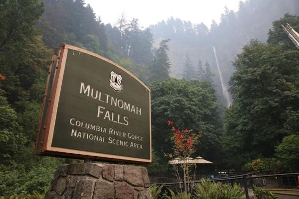 <p>The Multnomah Falls sign on Sept. 6, 2017 as the Eagle Creek Fire looms nearby.</p>