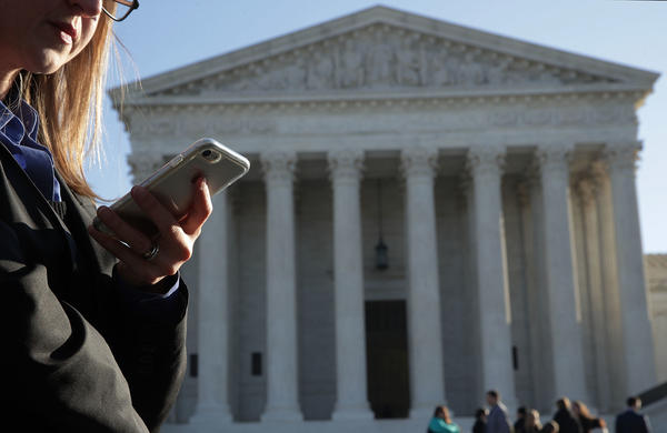 A woman checks her cellphone as she waits in line to enter the Supreme Court on Wednesday to hear arguments in <em>Carpenter v. United States </em>about the government's access to cellphone data.
