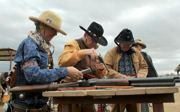 Members of the Single Action Shooting Society load their rifles and pistols at the Iron Hero match, including Dannette Ray of Boulder, Colorado (left), aka Maria Laveau.