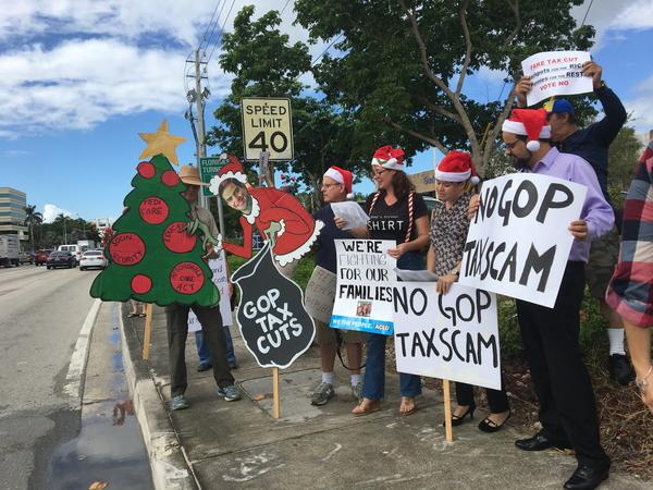 Protesters rallied outside of Sen.Marco Rubio's office in Doral singing their own versions of Christmas carols opposing the GOP tax bill.