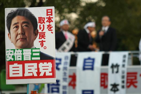 Supporters hold up posters of Japan's former Prime Minister Shinzo Abe at a rally in Osaka on Thursday. Considered a nationalist hawk, Abe is expected to become prime minister for a second time after parliamentary elections Sunday.