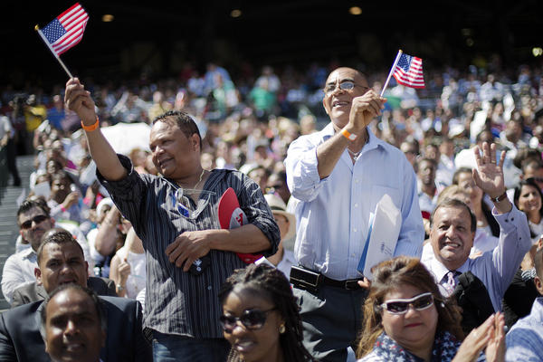 Hector Colon (left) and Victor Duran, both of the Dominican Republic, wave American flags after being sworn in during a naturalization ceremony in Atlanta on Tuesday.
