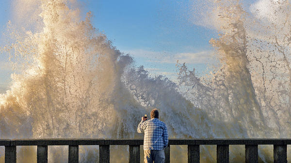 Bo Sailor watches Thursday as high surf crashes into the seawall before spilling onto Channel Drive in Montecito, Calif. An ocean-water-quality advisory was issued for the area after a number of December and early-January storms pummeled Southern California with heavy rainfall.