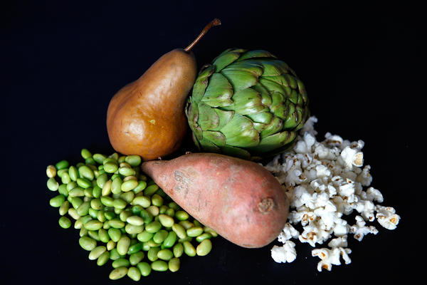 These fiber-rich foods altogether offer about 28.5 grams, or a woman's daily recommended intake. Clockwise from top left: one pear, 6 grams of fiber; medium artichoke, 7 grams; 1 ounce of popcorn, 3.5 grams; 1 medium sweet potato, 4 grams; 1 cup edamame, 8 grams.