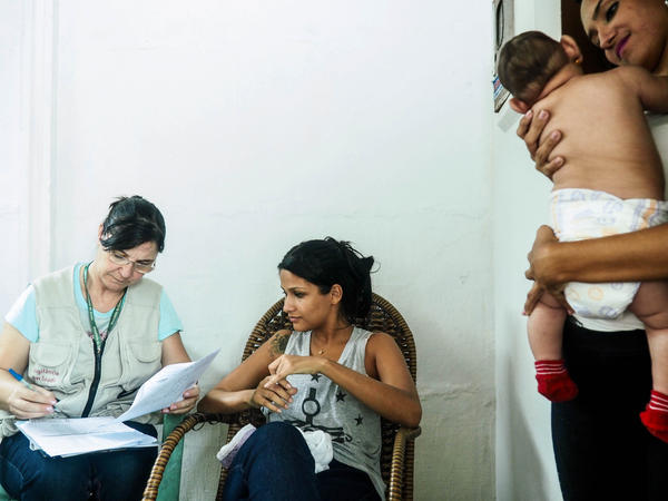 Marcia Andrade, an agent from Brazil's Ministry of Health, interviews Camila Alves, 22. A friend holds Alves' 2-month-old daughter.