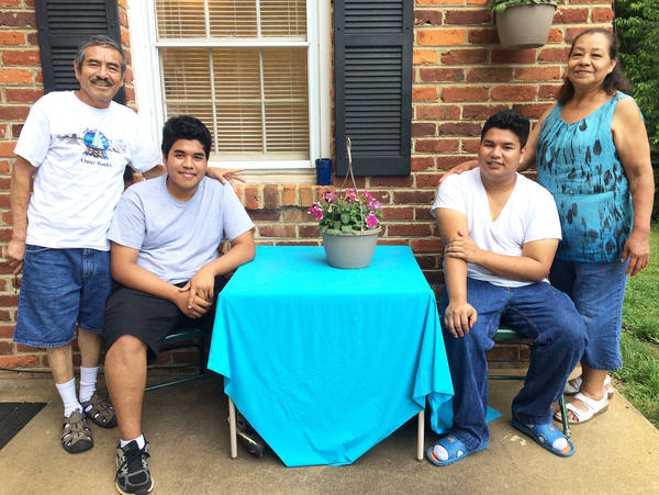 Edson Escobar, 16, (seated, left) and his brother Alex Escobar, 18, (right), with their grandparents Ricardo and Sara Tejada in central Virginia. Edson and Alex came to the U.S. from El Salvador separately two years apart to escape their abusive father.