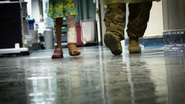 Ameera, 6, walks with assistance at the Craig Joint Theater Hospital at Bagram Airfield, Afghanistan. She is recovering from a gunshot wound sustained when she was caught in a firefight between U.S. and Afghan soldiers and Taliban insurgents.