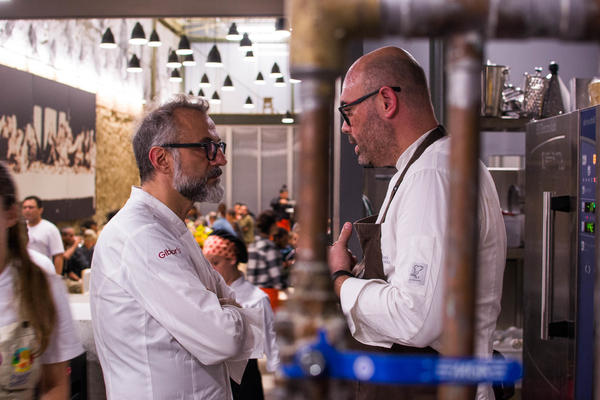 Chefs Massimo Bottura and Carlos Garcia talk in the kitchen during the dinner service.