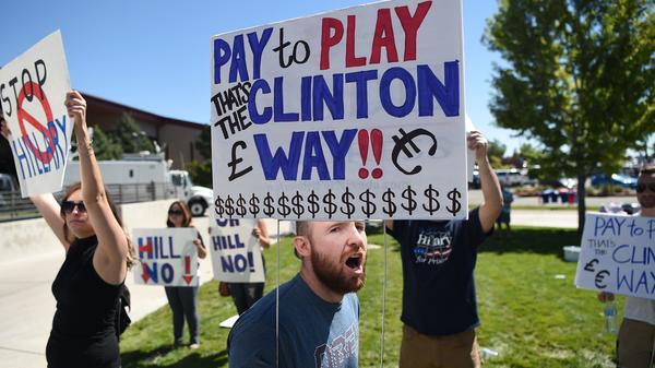Protesters shout as people wait to enter a Hillary Clinton campaign event last month in Nevada. Donald Trump is calling for a special prosecutor to investigate allegations of pay-to-play by Clinton, but the history of independent counsels and special prosecutors suggests they don't always remove politics from the process.