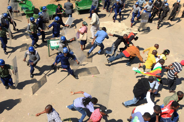 Zimbabwe's riot police clash with protesters who oppose the introduction of bond notes by the country's Reserve Bank, in the capital, Harare, on Aug. 17. The bank says the notes will be equivalent to the U.S. dollar, which serves as the country's main currency. But the announcement has prompted many to withdraw their U.S. dollars from banks.