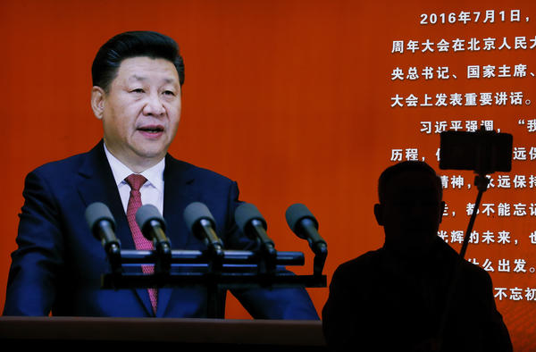 A man takes a selfie near a picture of Chinese President Xi Jinping at an exhibition at a military museum in Beijing on Monday. Xi is expected to use an important meeting this week to re-emphasize his anti-graft campaign. Analysts say the campaign is also used to go after rival factions within the Communist Party.