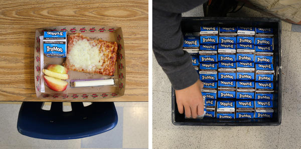 A lunch left behind by a student at Franklin Sherman Elementary School. Unopened milk from lunch is boxed up to be sent to the food bank. Cheese sticks are also donated.