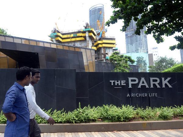 """Men walk past Mumbai's """"Trump Tower"""" in July 2015. It is still under construction."""