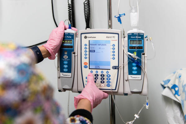 The nurse programs a pump to administer Luke Whitbeck's enzyme-replacement therapy in October 2016.