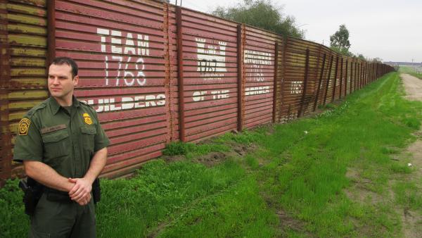 Border Patrol agent James Nielsen stands near the original landing-mat border fence near Chula Vista, Calif.