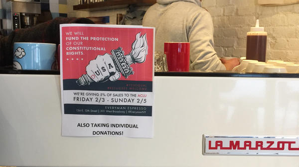 At Everyman Espresso in New York City's East Village, customers were greeted with a sign announcing a fundraiser to help defend immigrants.
