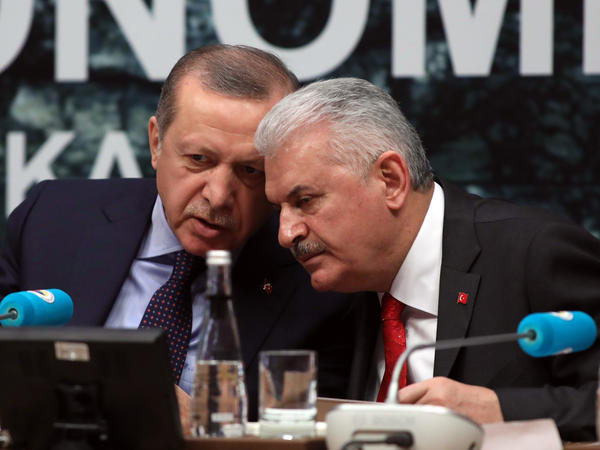 President Recep Tayyip Erdogan (left) and Prime Minister Binali Yildirim speak at the Turkish Union of Chambers and Commodity Exchanges Economic Council in Ankara on Feb. 7. Voters will decide in April whether to give Erdogan broad, new powers that would eliminate Yildirim's job.