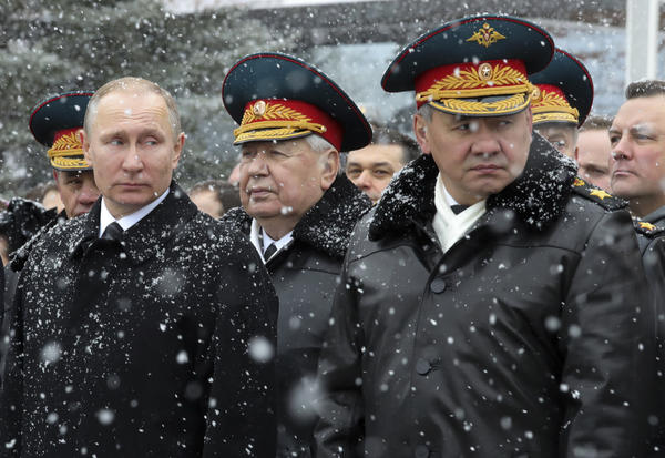 Russian President Vladimir Putin and Defense Minister Sergei Shoigu (far right) attend a wreath-laying ceremony at the Tomb of the Unknown Soldier in Moscow on Thursday. Shoigu announced the use of 162 Russian weapons in Syria on the eve of the Defenders of the Fatherland national holiday, celebrated in Russia on Thursday in honor of the nation's military.