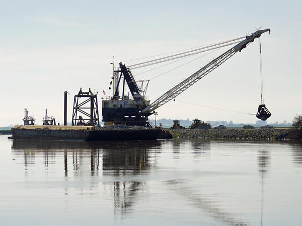 A dredge drops rocks onto a damaged levee in California's delta.