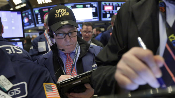 "Trader Richard Cohen wears a ""Dow 21,000"" cap as he works on the floor of the New York Stock Exchange on Wednesday."