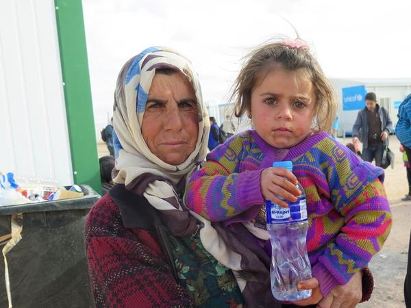 Enshera Mustafa holds her four-year-old granddaughter Nada outside a clinic near the Syrian-Jordanian border. Jordan sealed the border with Syria after a bombing last year and now allows a small number of refugees across for medical treatment before sending them back.