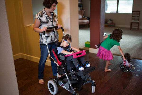 Kathleen helps Gideon into his chair while his sister Genevieve plays with her dolls, one of whom has a wheelchair.