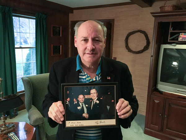 Brian Rusk voted for President Trump after his two other picks dropped out of the race. Here, the longtime Republican activist holds a picture of himself with former President George H.W. Bush.