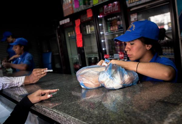 A bakery worker grabs a bags of bread in Caracas, Venezuela, last month. Venezuelan bakeries are the latest industry to find themselves in the cross-hairs of President Nicolas Maduros administration, as bread lines grow in the capital Caracas. The government has ordered bakers to use scarce supplies of flour to produce price-controlled loaves.