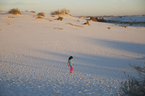 A girl plays in the sand during the evening sunset stroll.