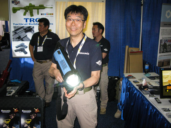 Hiro Yazawa of Japan Cell displays a spotlight weapon that sells for $5,000 at the Border Security Expo in San Antonio on Tuesday.