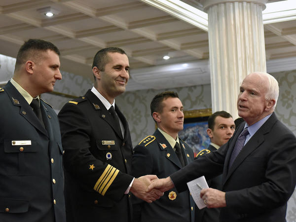 Sen. John McCain, right, shakes hand with Montenegrin army officers in Podgorica, Montenegro on April 12. McCain has congratulated Montenegro for its upcoming NATO membership.