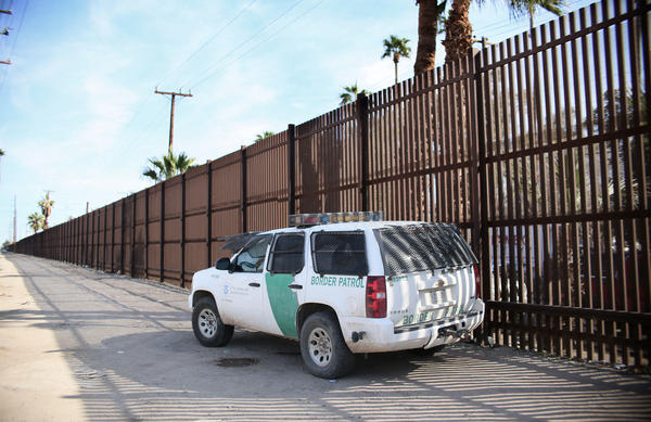 A Border Patrol agent looks over the U.S.-Mexico border wall in Calexico, Calif., on Jan. 31. Apprehensions at the southern border fell dramatically: from more than 40,000 per month late last year to 18,754 in February, and just 12,193 in March.