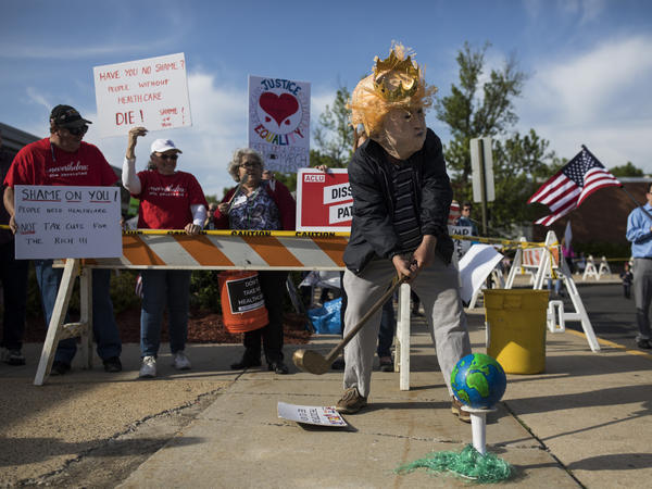 A demonstrator wearing a Donald Trump mask pretends to play golf with the globe. Protesters had gathered before a town hall meeting with Rep. Tom MacArthur, R-N.J., author of an amendment credited with enabling passage of the American Health Care Act.
