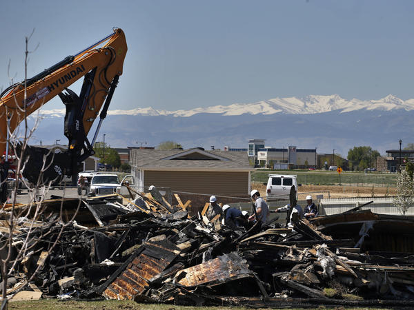 On May 4, workers dismantle the charred remains of a house in Firestone, Colo., where an unrefined gas line leak explosion killed two people in April.