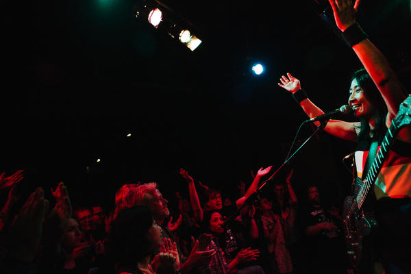 Naoko leads the crowd in a clapping beat at D.C.'s Black Cat, where the band played to a packed room.