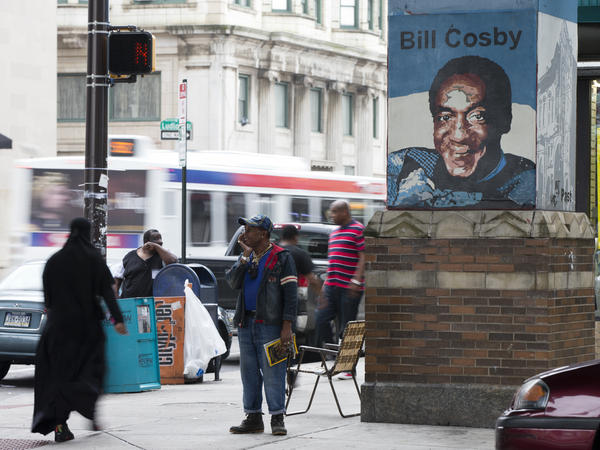 People walk past a mural depicting Bill Cosby in the entertainer's hometown of Philadelphia in 2015. Another Cosby mural in the city was painted over after sexual assault allegations against him came out.