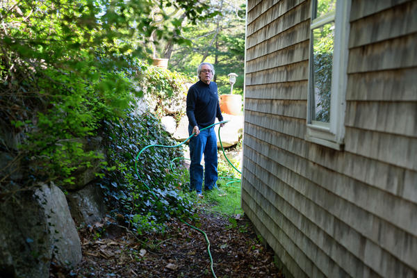 Greg unwinds a hose while doing some yardwork. Along with his failing memory, Greg has been experiencing secondary symptoms including paranoia, depression and slow healing.