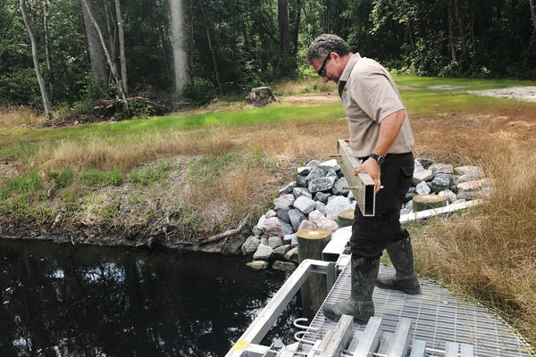 Chris Lowie, refuge manager at the Great Dismal Swamp National Wildlife Refuge, demonstrates how the newly installed water control structures work.
