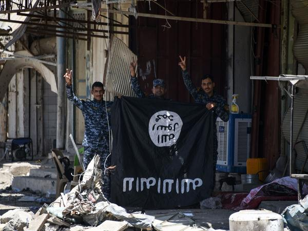 Iraqi government forces flash a victory sign while holding an upside-down Islamic State flag in western Mosul on June 9. As ISIS loses territory, it's still exhorting its supporters to keep fighting.