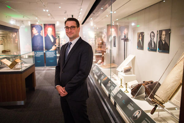Religion curator Peter Manseau stands in the National Museum of American History's new exhibit, <em>Religion in Early America</em>.