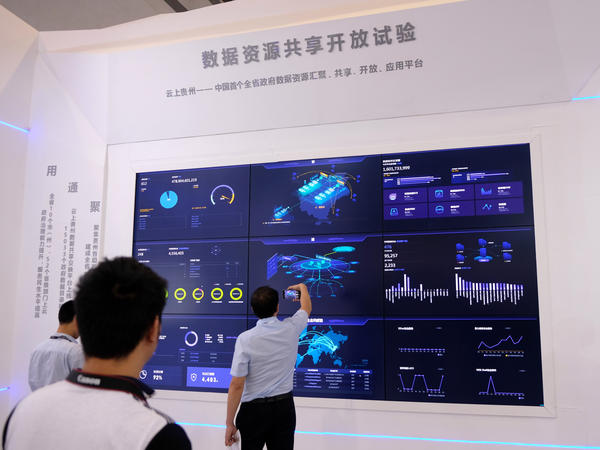 Visitors look at a booth explaining the Chinese government's plans for the big-data industry at an expo in southwest China's Guizhou province.