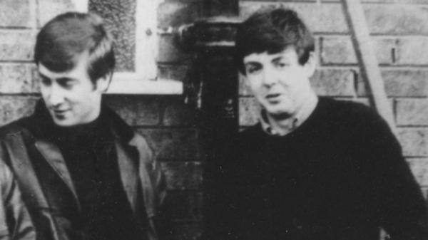 John Lennon (left) and Paul McCartney, pictured here circa 1960, met as teenagers in July 1957.