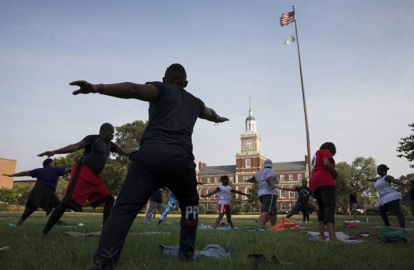 "Participants stretch during a ""yoga on the yard"" class, one of Howard University's sesquicentennial celebration events that was open to anyone in Washington, D.C., who wanted to attend. The university is trying to foster better relations with the surrounding community."