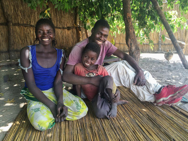 Likezo Nasilele and her husband, Chipopa Lyoni, with one of their four children in the courtyard of their home in rural Zambia. They were one of hundreds of families who received regular cash payouts as part of a government experiment.
