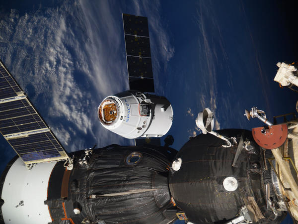 In this photo taken by Russian cosmonaut Sergey Ryazanskiy, the SpaceX Dragon capsule arrives at the International Space Station on Wednesday, stocked with scientific equipment, supplies — and ice cream.