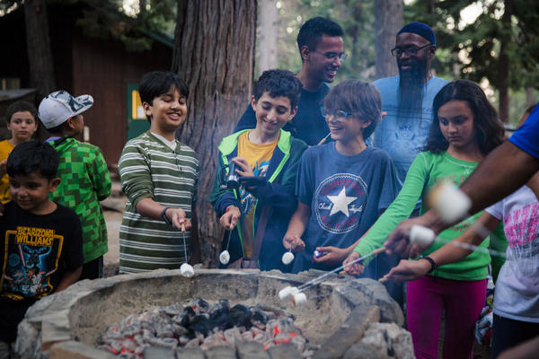 Campers roast halal marshmallows to make s'mores.