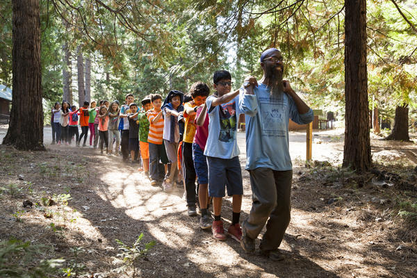 Ronald Chavez Hassan leads kids in a trust walk at the Muslim Youth Camp of California. He has been a teacher at the camp for 25 years.